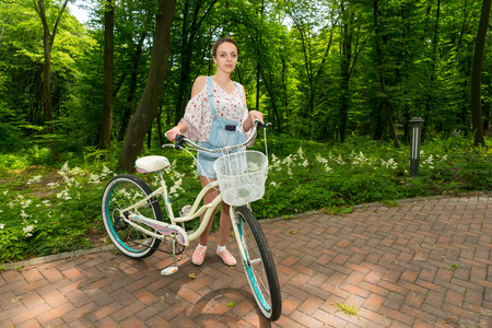 Smiling girl wearing denim overalls and a loose-fitting blouse standing with her bicycle on bricks in a park Stock Photo