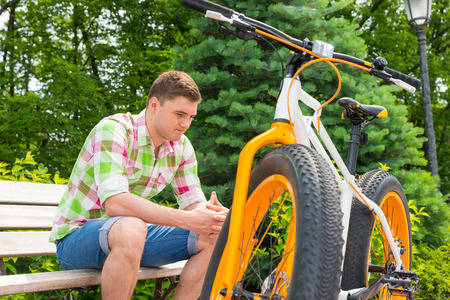 Pensive young man sitting on bench near bike with fat tires in beautiful green park