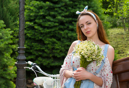 Young attractive romantic female holding large bouquet of little white flowers while leaning on railing of a bridge outside
