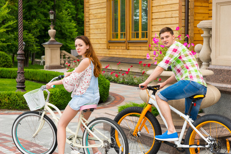 tryst: Beautiful couple turned around and looking into the camera while riding bikes against the background of luxury home in a park