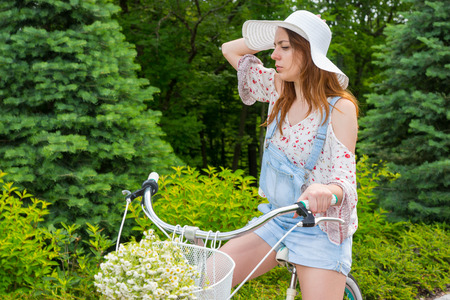 Young girl wearing a beautiful white hat sitting on her bicycle with a bouquet of little white flowers in a basket in a park with background of different trees Stock Photo