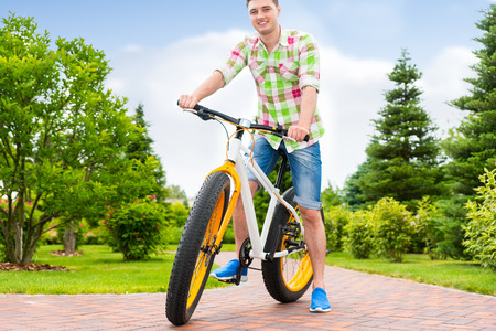 Fabulous handsome man wearing a green and red plaid shirt sitting on his bicycle in a park with background of different trees