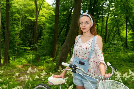 Fasionable Frauen tragen Jeans-Overall und eine locker sitzende Bluse mit ihrem Fahrrad in einem Park