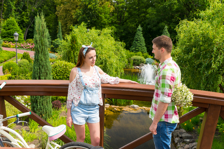 Young romantic female and male holding large bouquet of little white flowers behind the back standing on a footbridge near bicycles  and smiling outside with background of different trees and fountain