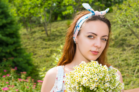Portrait of young girl holding large bouquet of little white flowers while standing in the park