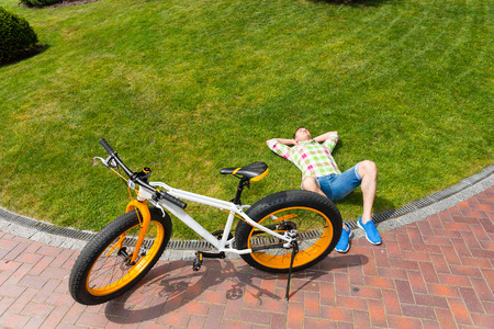 Top down view on relaxing man laying down on grass next to yellow and white fat tire bicycle with copy space