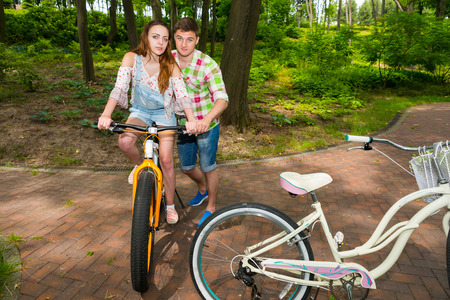 acquaintance: Handsome male in green and red plaid shirt  teaches his girlfriend riding a bicycle in a park Stock Photo