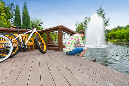 Guy in green and red plaid shirt sitting on the wooden deck after biking in a park with fountain in a background