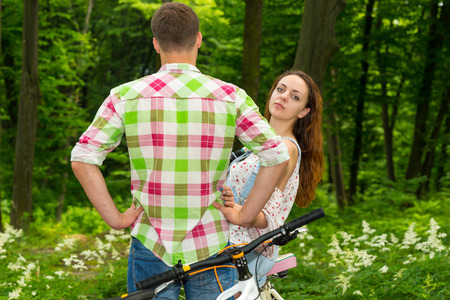 Young girl looks out from a guy in green and red plaid shirt and looking into the camera after biking in a park