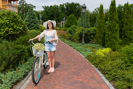 Attractive female wearing a white hat standing on footpath near her bicycle with a bouquet of little white flowers in a basket in a park with background of different trees