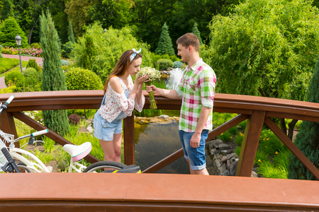 Young romantic girl sniffing the bouquet of little white flowers as a present from her boyfriend standing on a footbridge near bicycles outside with background of different trees and fountain Stock Photo