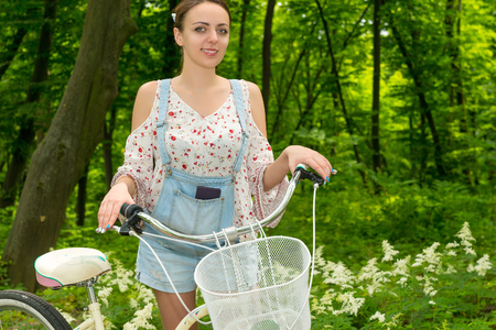 Portrait of smiling girl wearing denim overalls and a loose-fitting blouse with her bicycle in a park