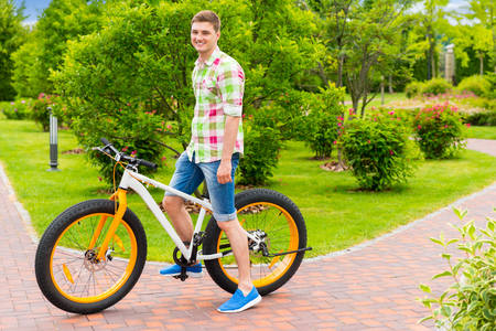 Happy smiling  guy wearing a green and red plaid shirt sitting on his bicycle in a park with background of different trees