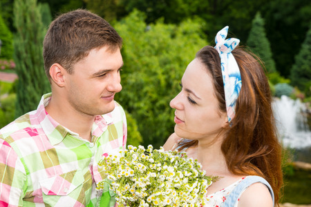 Young attractive and romantic couple with bouquet of little white flowers looking at each other while having a date with background of different trees and fountain Stock Photo