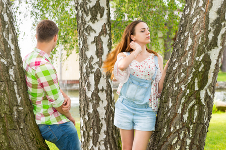 Young couple leaning on trees in a park with fountain and different trees Stock Photo