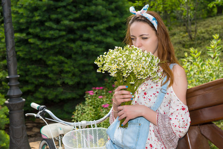 Single beautiful young woman smelling large bouquet of little white flowers while leaning on railing near bike outside