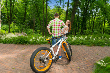 Young female looks out from a guy in green and red plaid shirt and looking into the camera after biking in a park