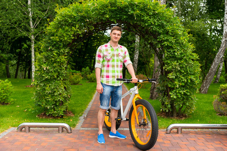 Handsome male standing on the footpath in front of arch made of bushes with bike in a park