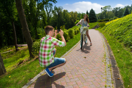 Man in green and red plaid shirt taking a photo of his girfriend sitting on a bike with a bouquet of little white flowers in a basket in a park