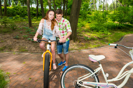 red plaid: Guy in green and red plaid shirt  teaches his girlfriend riding a bicycle in a park or forest