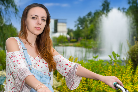 tryst: Portrait of a happy female wearing denim overalls and a loose-fitting blouse on a bike in a park with fountain, colorful flowers, bushes and different trees in a background