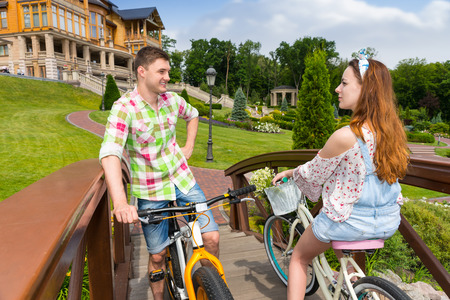 tryst: Meeting of a girl and guy in green and red plaid shirt while they are riding on bikes on footbridge in the beautiful  park