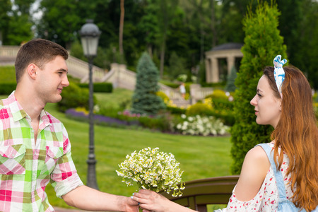 tryst: Young man in green and red plaid shirt gives a girl a bouquet of little white flowers on footbridge in park
