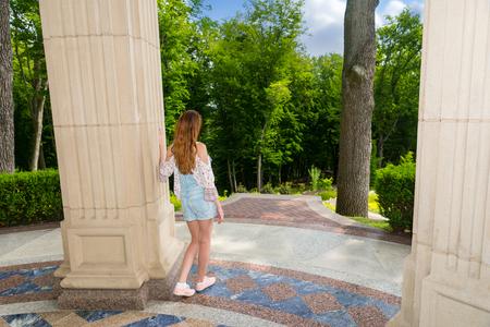 empedrado: Vista lateral de la hembra joven contemplativa de pie cerca de la pared de piedra árboles afuera enfrentan en el parque o en el patio