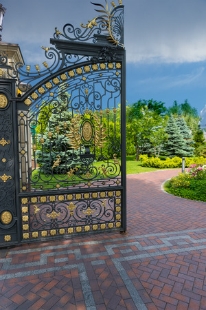 victorian fence: Part of luxury iron gate to the entrance of a beautiful park Stock Photo