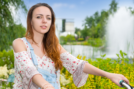 Portrait of a young woman wearing denim overalls and a loose-fitting blouse on a bike in a park with fountain, colorful flowers, bushes and different trees in a background Stock Photo