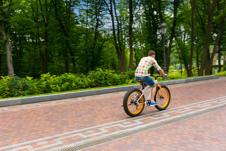red plaid: Male in green and red plaid shirt riding a bike on a footpath in a park Stock Photo