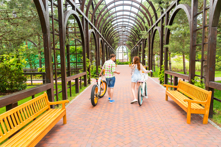 Young couple with modern bikes spending their free time in archway in a park Stock Photo