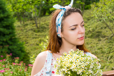 Portrait of a thoughtful young girl holding large bouquet of little white flowers while standing in the park Stock Photo
