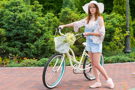 Young woman wearing a white hat standing near her bicycle with a bouquet of little white flowers in a basket in a park with background of different trees Stock Photo