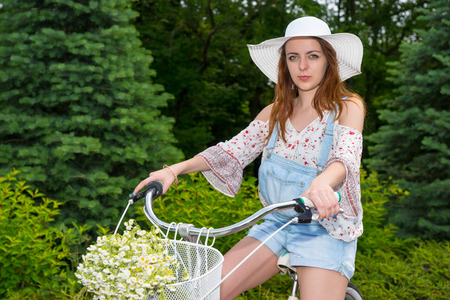 Attractive female wearing a beautiful white hat sitting on her bicycle with a bouquet of little white flowers in a basket in a park