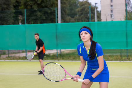 male tennis players: Female and male tennis players wearing a sportswear playing doubles at tennis court at early morning