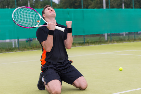 Young male player fell on his knees and made a fist because of the win in a match  at the tennis court Stock Photo