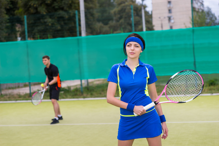 male tennis players: Portrait of female and male tennis players wearing a sportswear playing doubles at tennis court at early morning Stock Photo