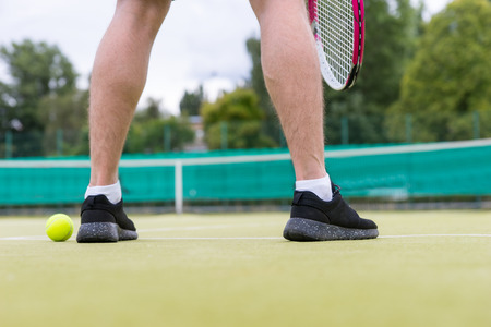 male tennis players: Male tennis players legs during the game wearing a sportswear on green grass court outdoors Stock Photo
