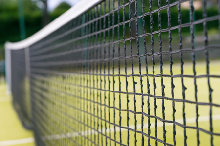 Close up of tennis net on empty grass tennis court outdoors in summer or spring Stock Photo