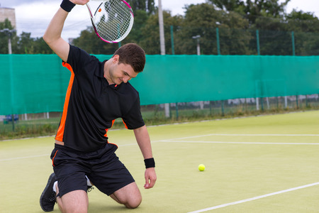 Angry male tennis player wearing a sportswear is going to break a racket while sitting on his knees because of the loss in tennis match