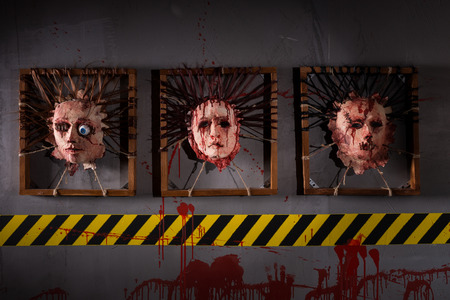 ghoulish: Ghastly skins from human heads stuck in square frames above yellow and black warning symbol Stock Photo