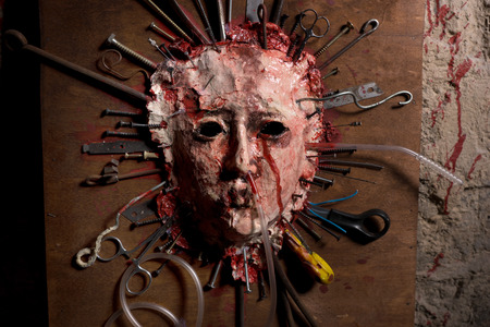 Close up of a skinned bloody face of a person stretched open on a wooden board with assorted sharp weapons alongside a blood splattered wall in a Halloween horror concept