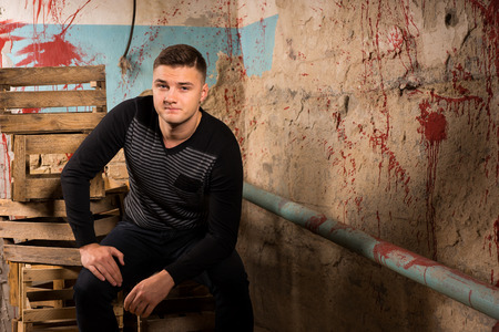 grisly: Handsome man sitting on empty packing crates in terrible basement in a Halloween horror concept