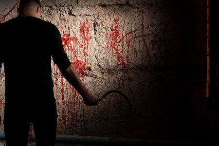 maniacal: Shadowy male figure holding sickle near blood stained wall for concept about murder and scary Halloween holiday Stock Photo