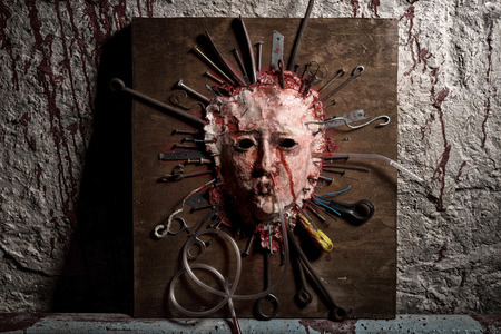 frightful: Frightful skinned bloody face of a person stretched open on a wooden board with assorted sharp weapons alongside a blood splattered wall in a Halloween horror concept