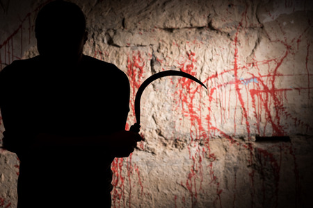 maniacal: Portrait of shadowy figure holding blade near blood stained wall for concept about murder and scary Halloween holiday