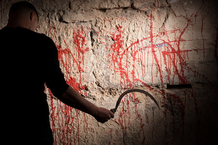 maniacal: Man holding a sickle near blood stained wall for concept about murder and scary Halloween holiday