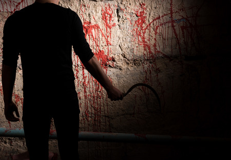 maniacal: Shadowy male figure holding blade near blood stained wall for concept about murder and scary Halloween holiday