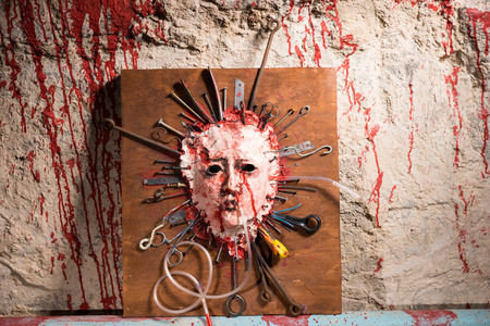 ghoulish: Skinned bloody face of a person stretched open on a wooden board with assorted sharp weapons alongside a blood splattered wall in a Halloween horror concept Stock Photo